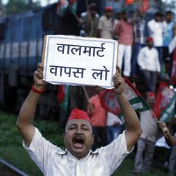 """A Samajwadi Party activist shouts slogans during a protest along railway tracks in Allahabad, India, Thursday, Sept. 20, 2012.  Angry opposition workers have disrupted train services as part of a daylong strike in India to protest rising diesel prices and the government's decision to open the country's huge retail market to foreign companies. The sign reads """"Take Walmart back."""""""