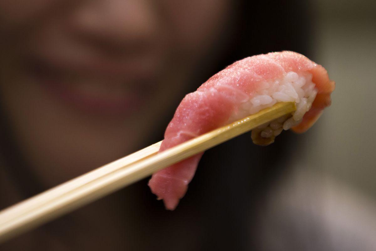 A piece of nigiri being held by chopsticks.