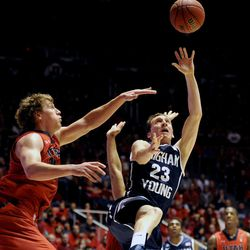 Brigham Young Cougars guard Skyler Halford (23) falls while going for a basket around Utah Utes center Dallin Bachynski (31) during a game at the Jon M. Huntsman Center on Saturday, Dec. 14, 2013.