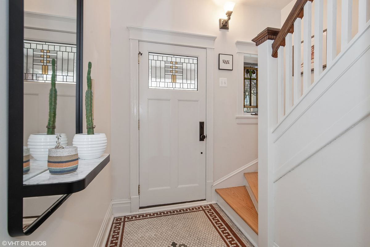 A foyer with original penny tile flooring and a door with an art glass window.