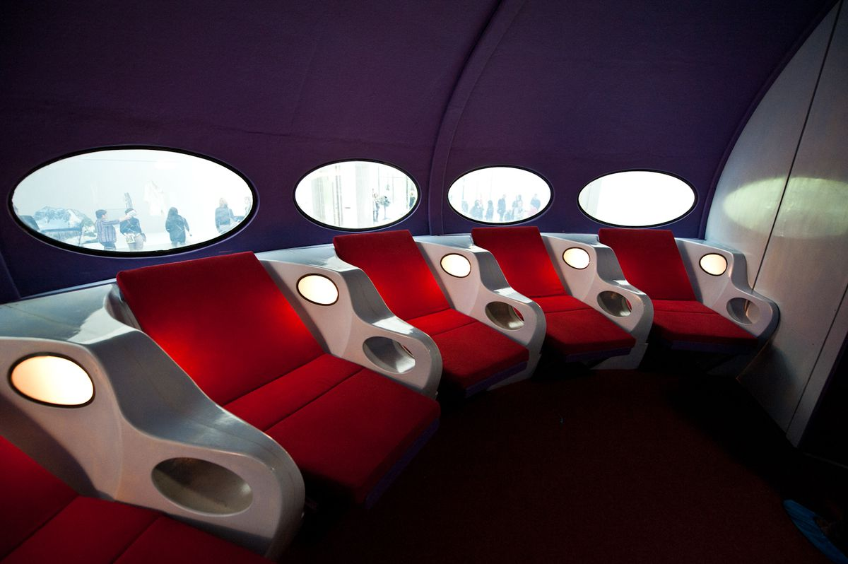The interior of a Futuro House in Netherlands. There are red seats resembling seats on a spaceship. The windows are oval and the walls are purple.