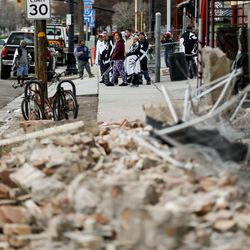Evacuees stand outside The Rescue Mission in Salt Lake City next to debris that fell after a 5.7 magnitude earthquake centered in Magna hit early on Wednesday, March 18, 2020.