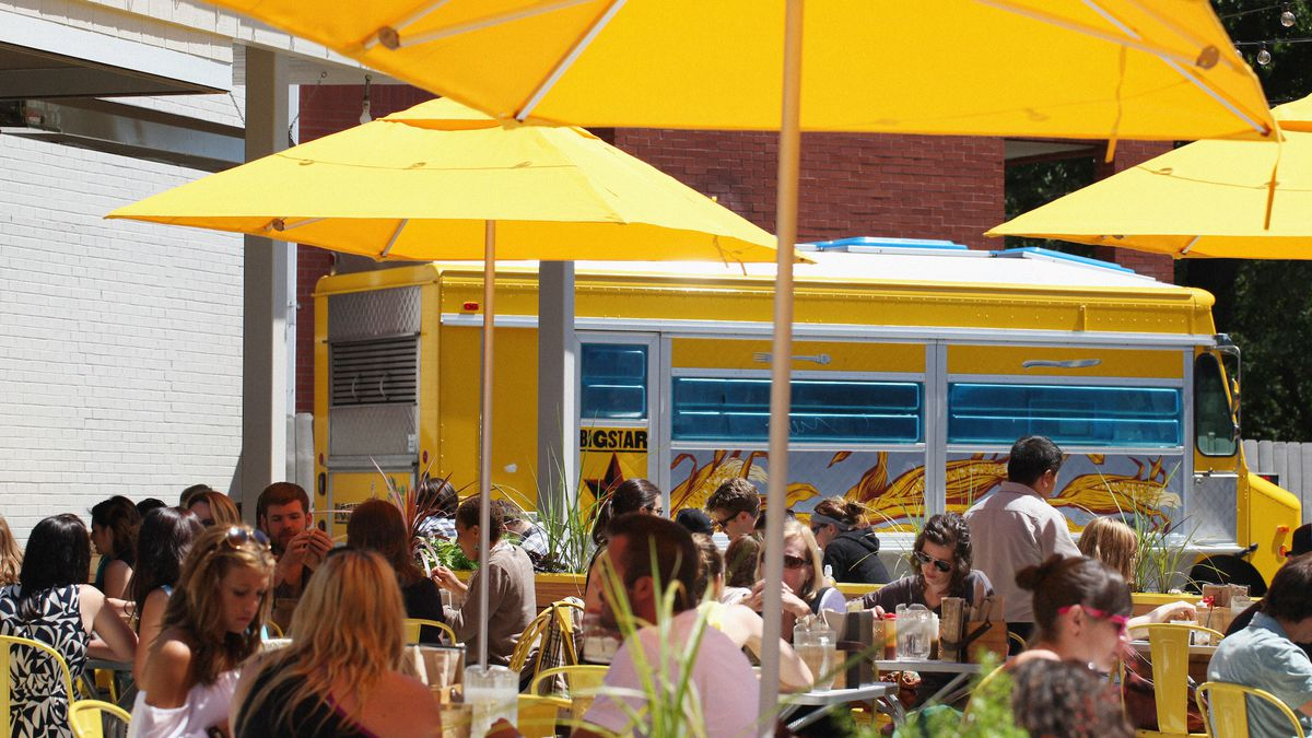 A packed patio on a sun-drenched day is filled with people and yellow umbrellas.
