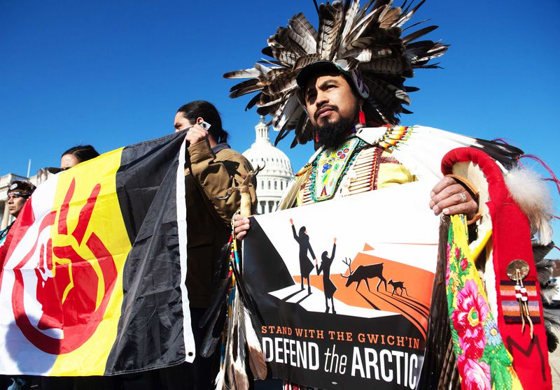"""A man in a feathered headdress and cape holds a sign that reads, """"Stand with the Gwich'in, Defend the Arctic."""" People beside him hold a banner representing a hand with two fingers up in a peace sign."""