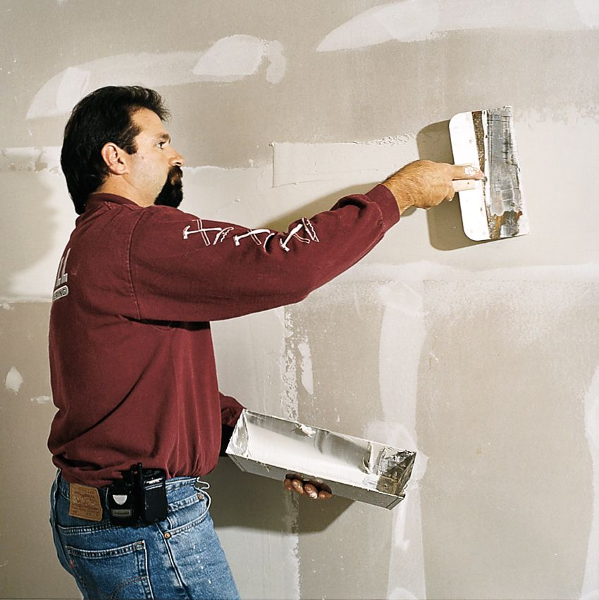 Man Applies Second And Third Coats Of Compound To Drywall
