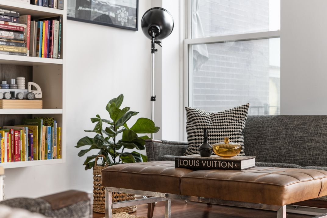 A living room area with a large window, a small brown leather chair that serves as a table, book shelves on the left, a planter, and a dark grey couch.