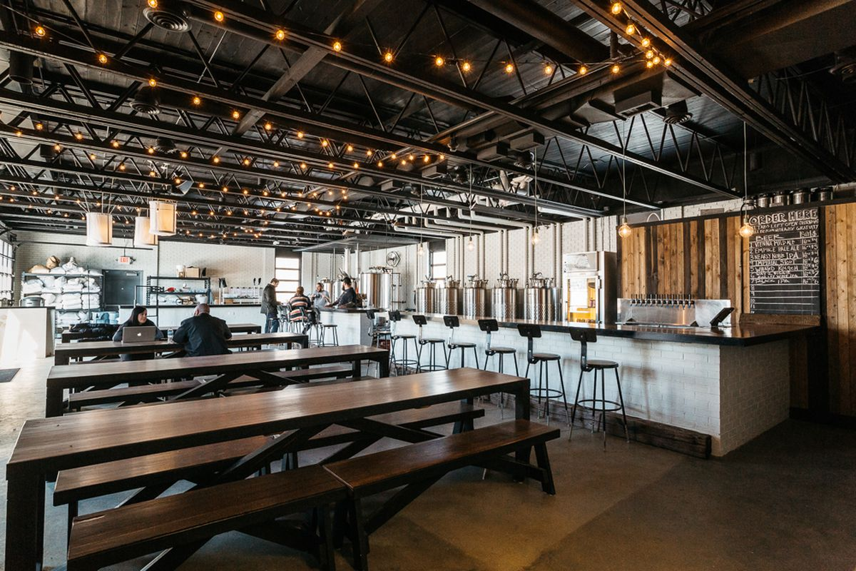 Customers sit at long communal tables inside Batch Brewing Company.