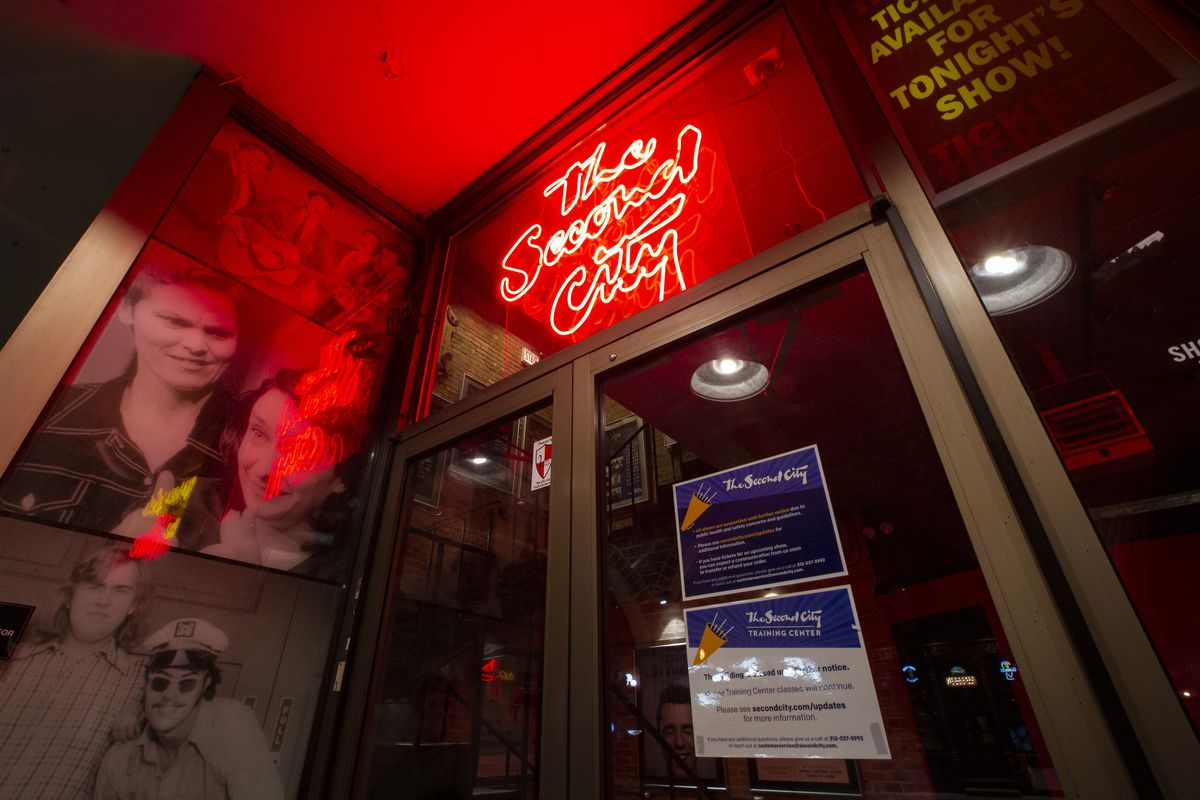 """A glass door with posters to the left and a red neon sign that says """"The Second City"""" above"""