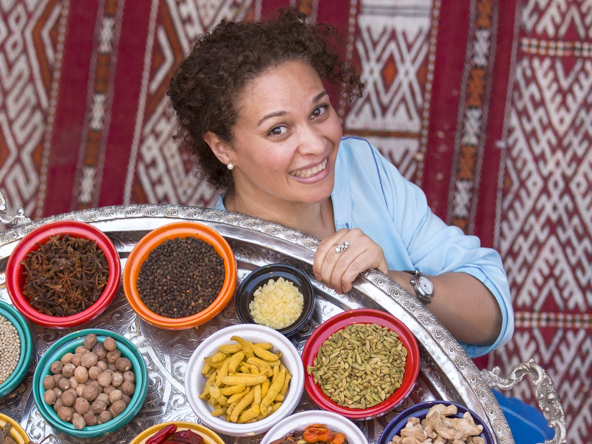From above, a woman, standing on a patterned carpet, carries a large silver platter containing small colorful bowls of raw ingredients