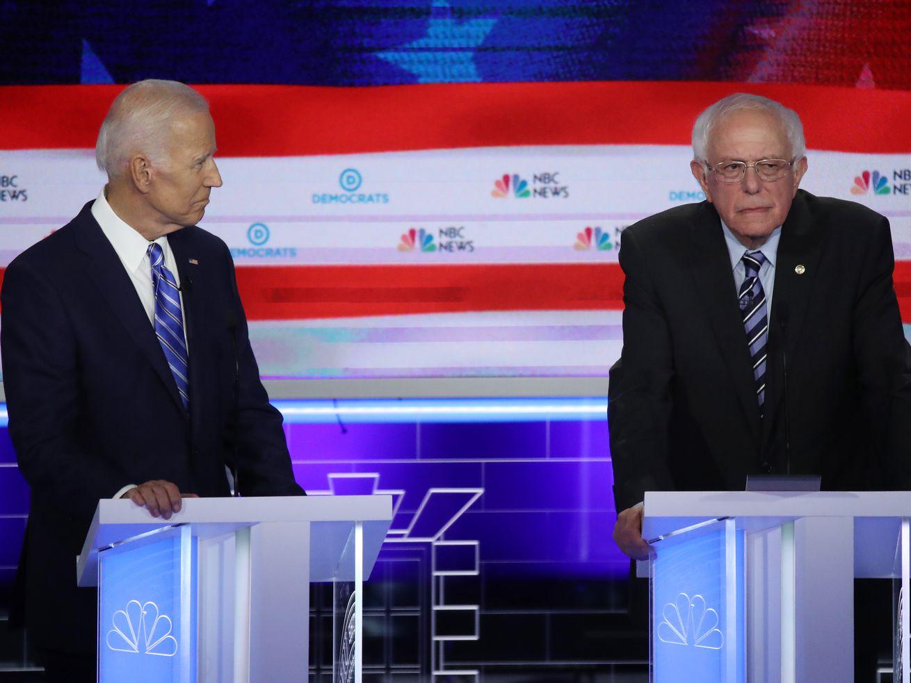 Former Vice President Joe Biden and Senator Bernie Sanders stand behind podiums onstage at the first Democratic debate of 2019.