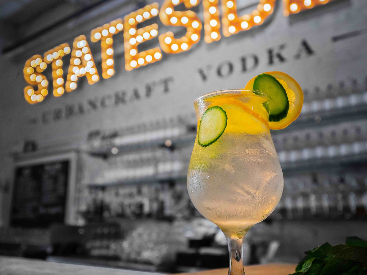 clear cocktail with lime and lemon garnish with sign in background that says stateside urbancraft vodka