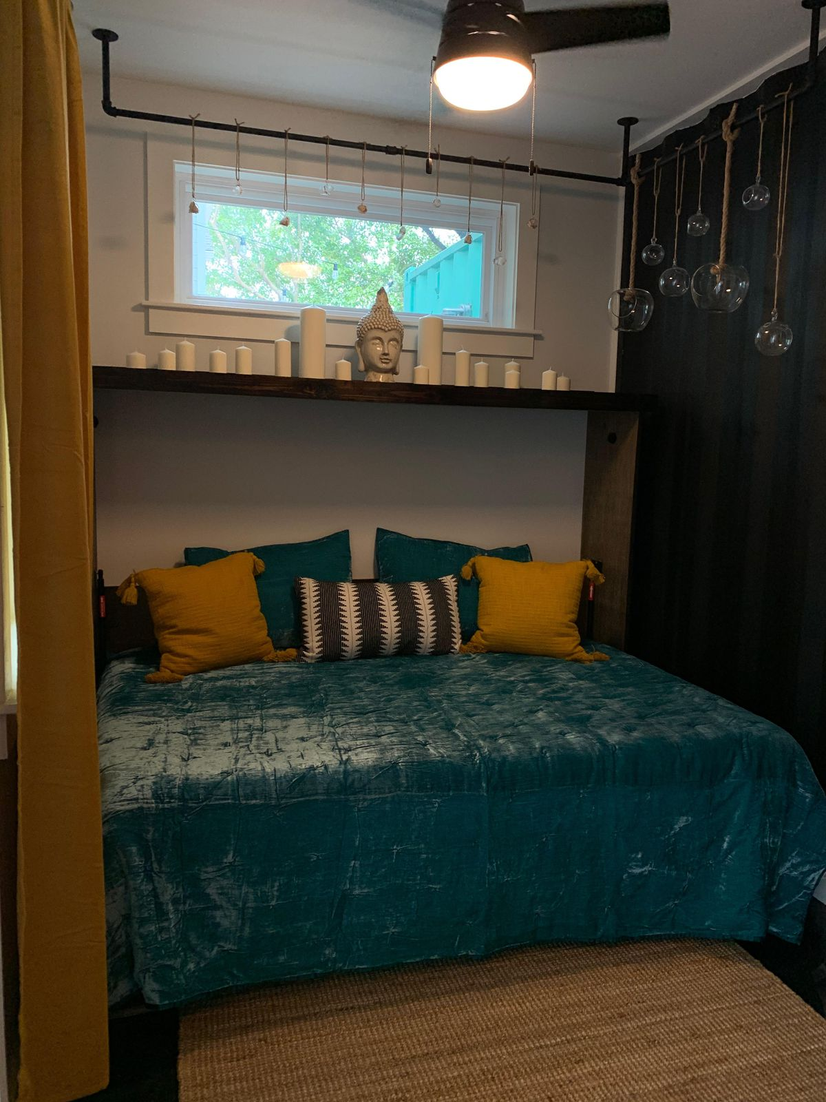A bedroom with a turquoise bedspread.