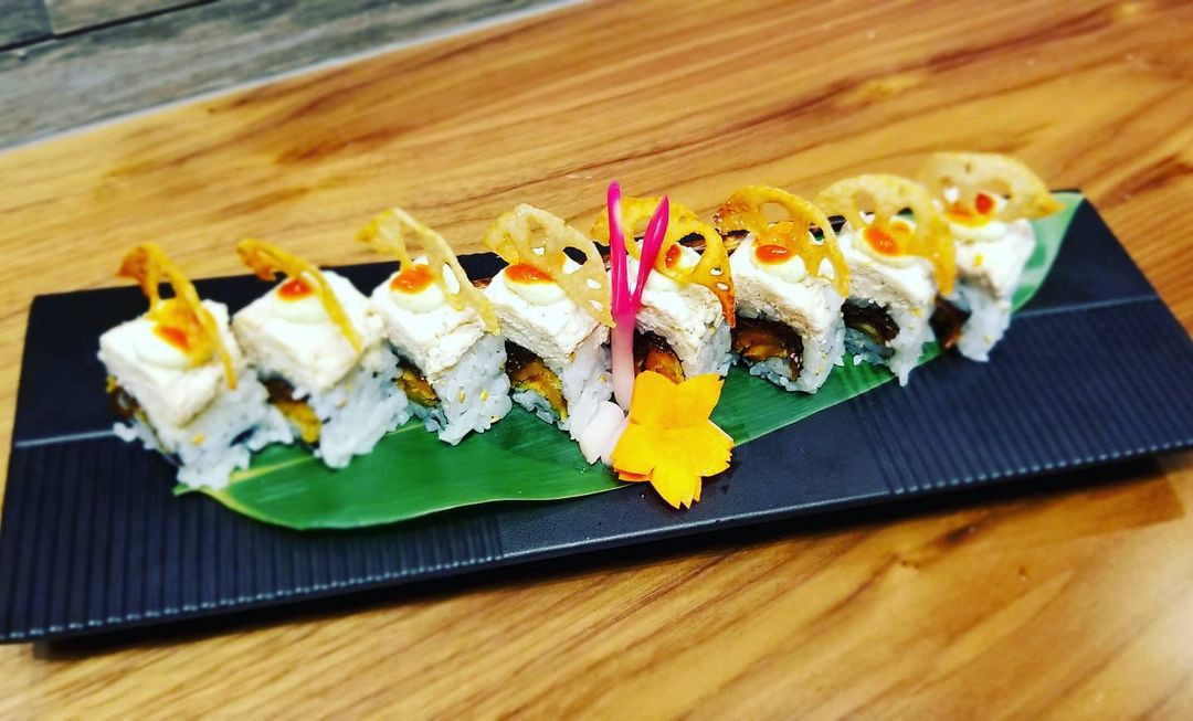 A black plate with vegan sushi