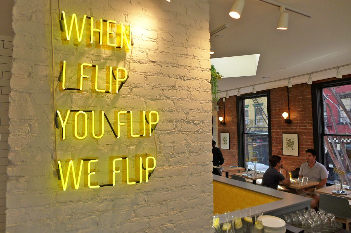 A yellow neon sign on a brick wall reads: When I flip, you flip, we flip...