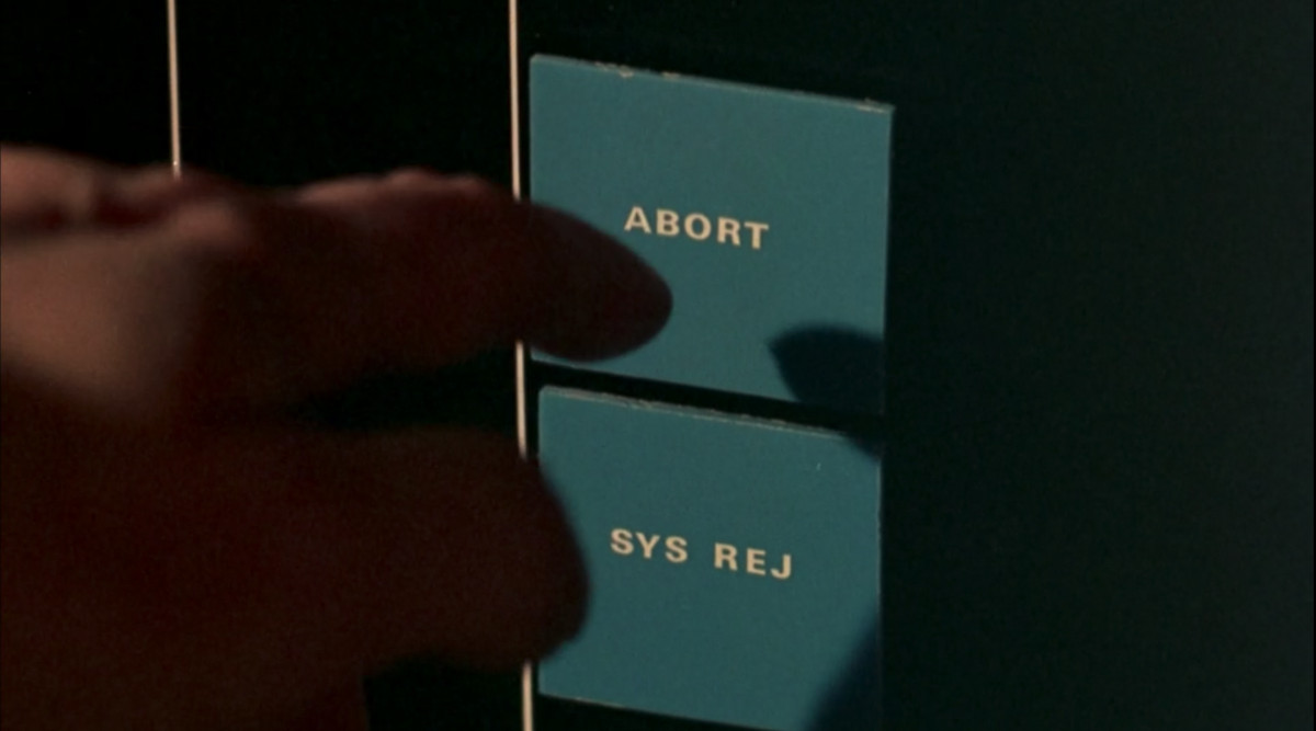 """Close-up of a finger reaching to touch the """"abort"""" button on an abortion machine in ZPG"""