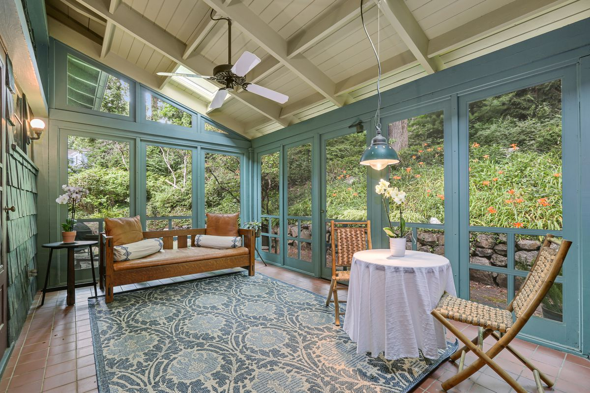 A light blue screened-in patio with rug and seating.