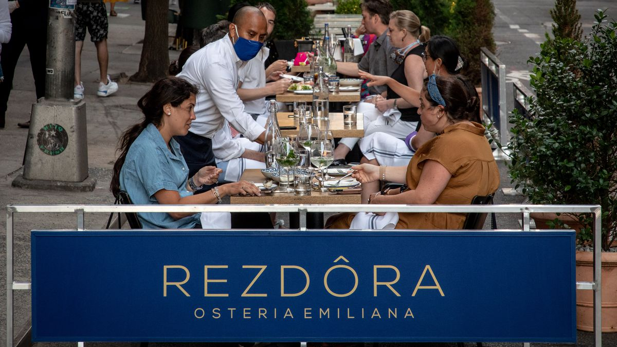 """A waiter pours water for two customers, who talk at an outdoor table in a row of other tables. In the foreground, there is a banner with the words """"Rezdôra Osteria Emiliana."""""""