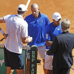 French team captain Guy Forget , center, shakes hand with U.S. player John Isner, left, as U.S. team captain Jim Courier, right, shakes hand with French player Jo-Wilfried Tsonga, after Isner defeated Tsonga, in the quarterfinal of the Davis Cup between France and U.S. in Monaco Sunday April 8, 2012.The U.S. team qualifies for the semi-final.(AP Photo/Remy de la Mauviniere)