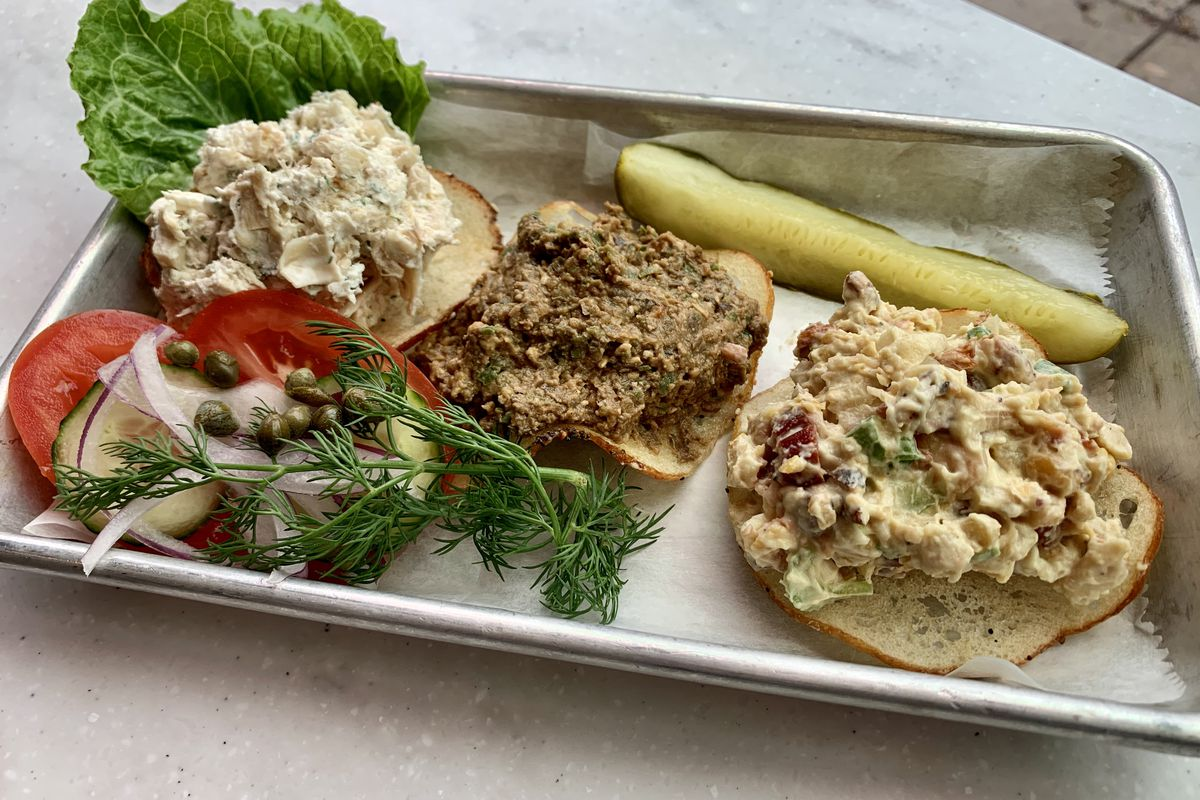 Vegan chicken salad, chopped liver, and tuna salad lined up on a tray beside a pickle.