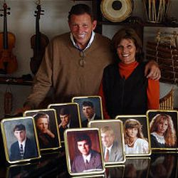 Richard and Linda Eyre stand behind portraits of their children.