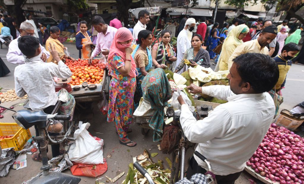 A woman covers her face while buying fruit and vegetables from a street stand