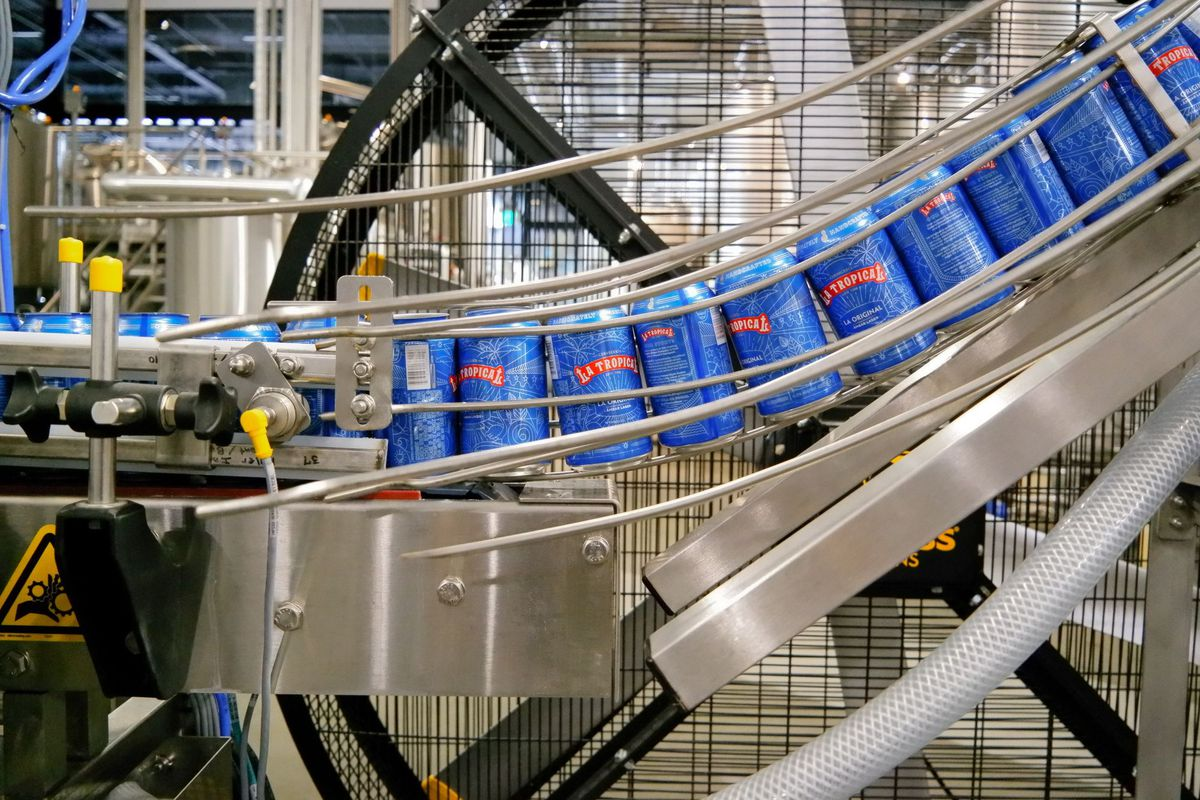 Beer on a silver rack moving down a production line
