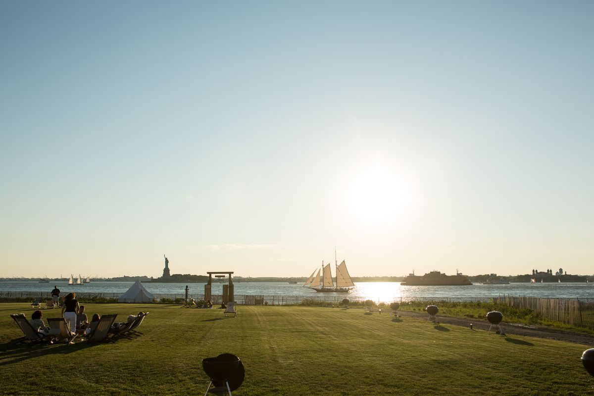 A lawn is in the foreground. In the distance is a body of water and the monument called the Statue of Liberty.