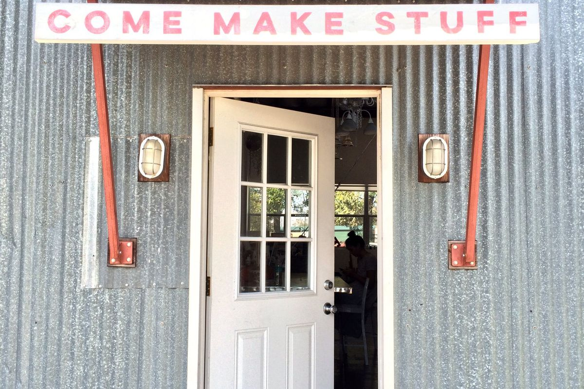 """Corrugated metal building with open door and sign that says """"Come Make Stuff"""""""