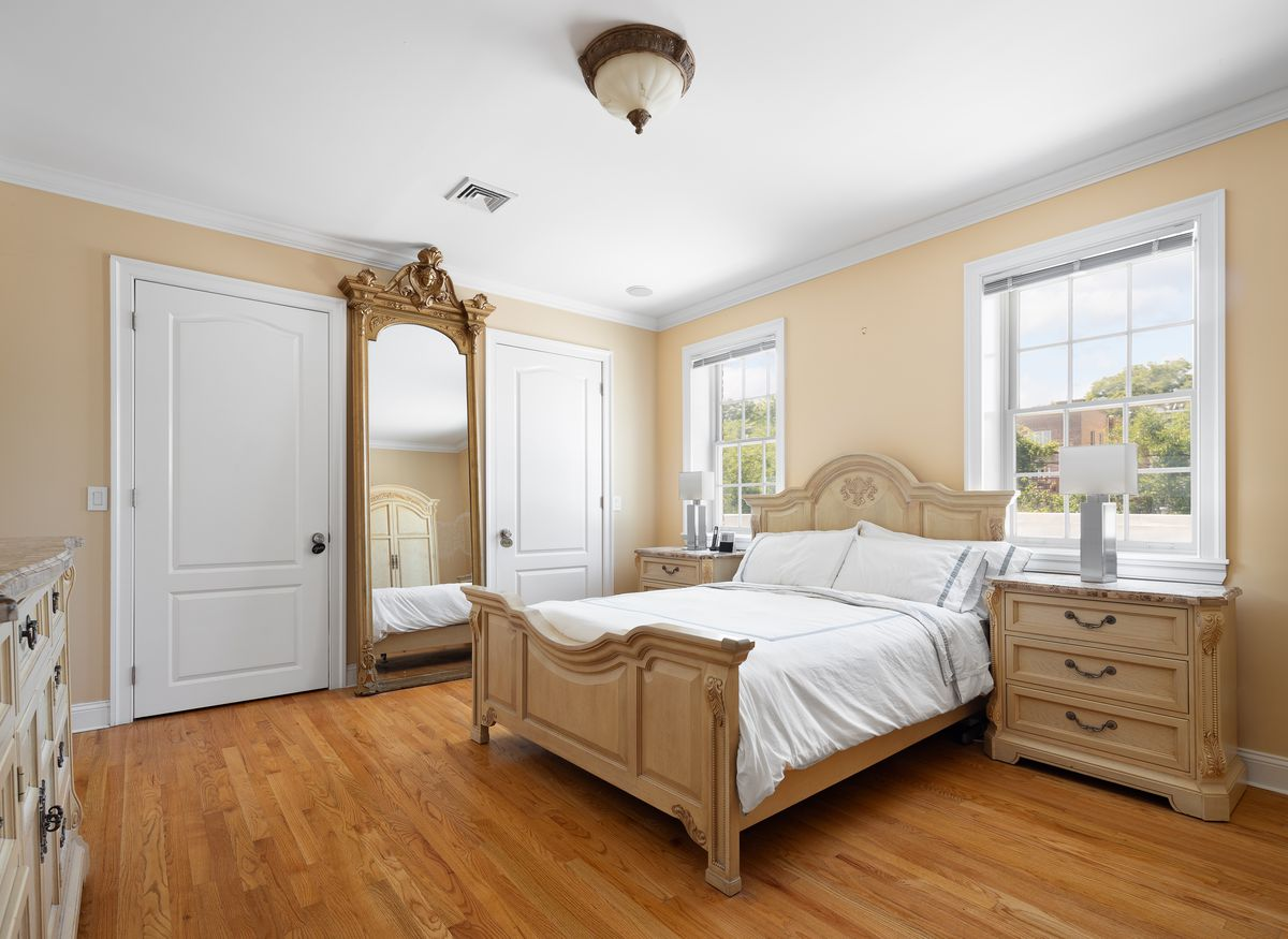 A bedroom with a medium-sized bed, beige walls, two windows, and hardwood floors.