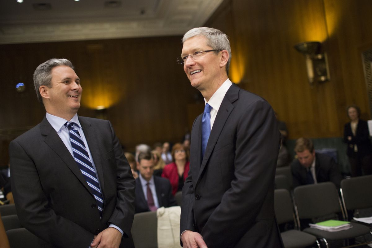 Apple CEO Tim Cook stands beside Apple PR executive Steve Dowling during a break in Cook's Senate testimony.