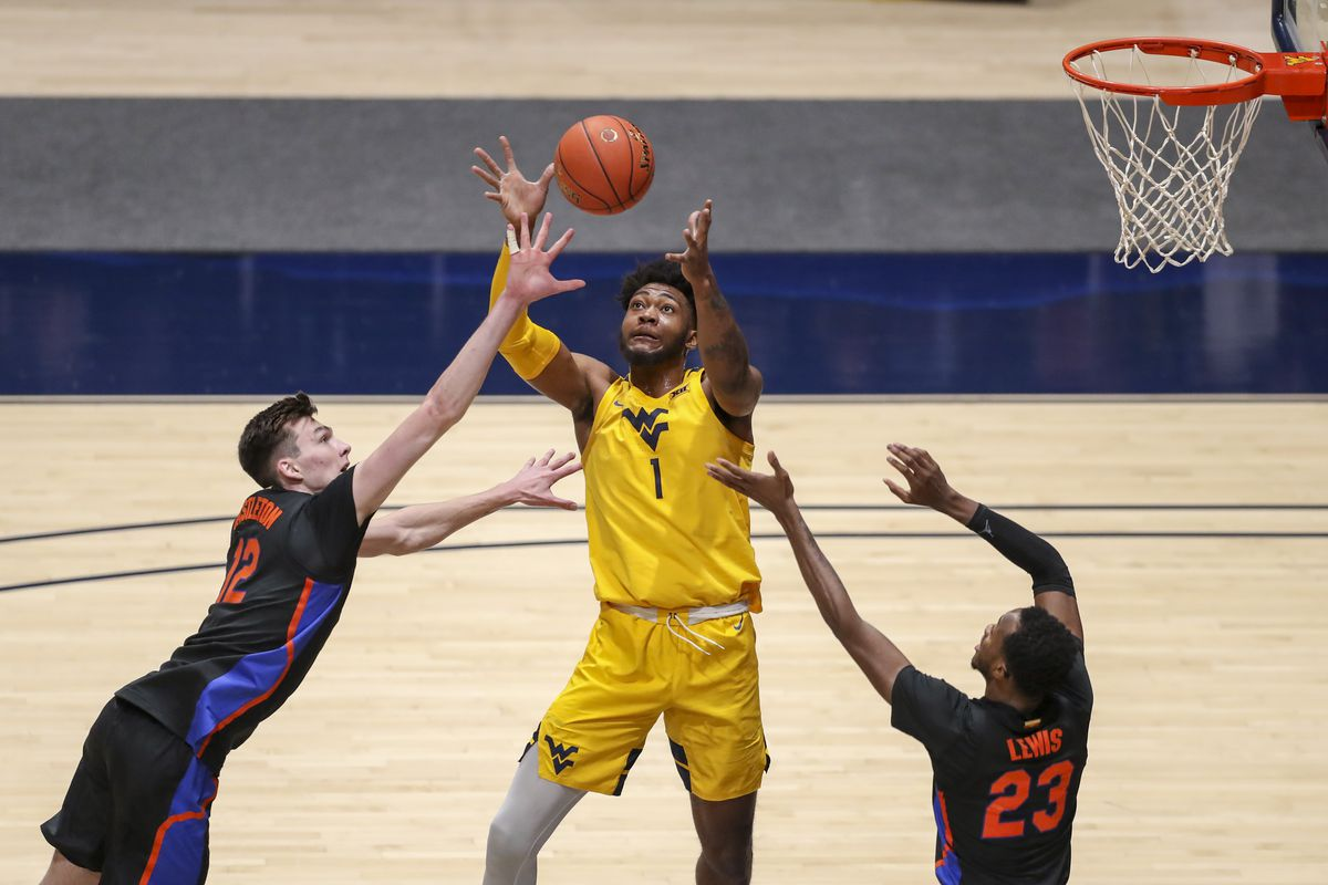 West Virginia Mountaineers forward Derek Culver catches a pass between Florida Gators forward Colin Castleton and guard Scottie Lewis during the second half at WVU Coliseum.