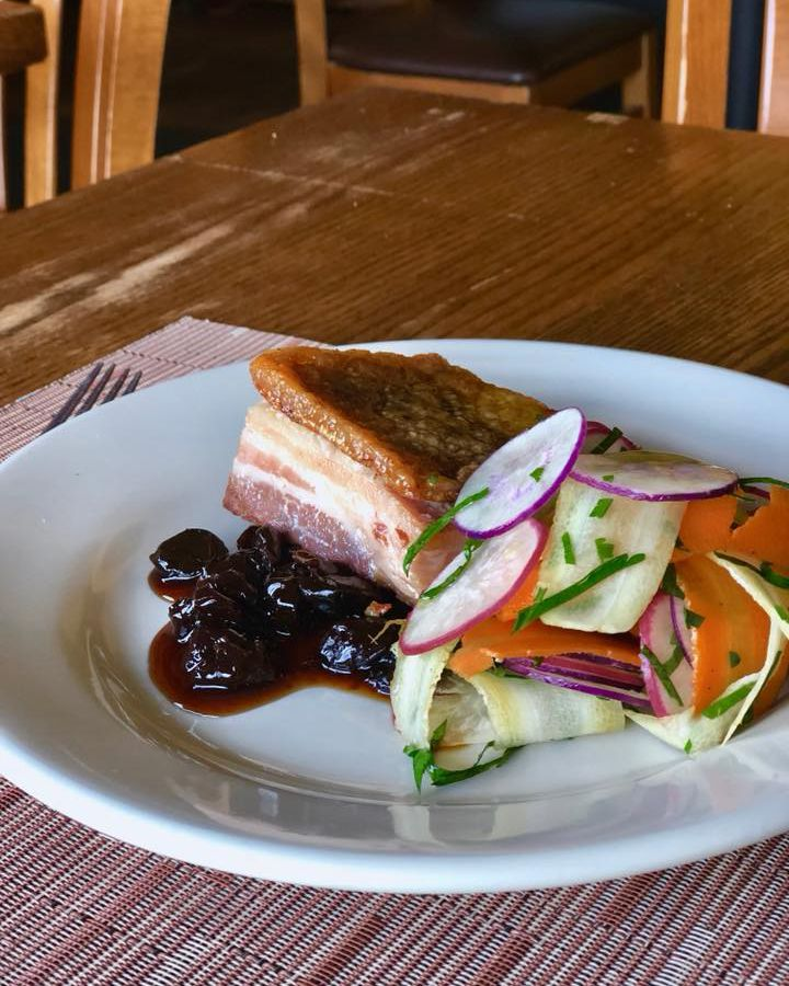 A large piece of pork belly sits on a plate with a jammy sauce and thinly sliced radishes and other vegetables