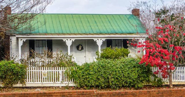 Small, one-story home with green metal roof and white picket fence.