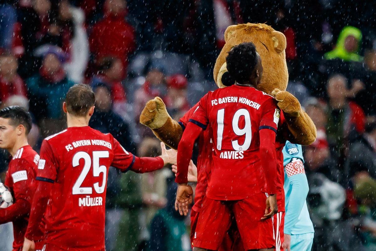 MUNICH, GERMANY - MARCH 17: Alphonso Davies of FC Bayern Muenchen and mascot Berni celebrate after winning the Bundesliga match between FC Bayern Muenchen and 1. FSV Mainz 05 at Allianz Arena on March 17, 2019 in Munich, Germany.
