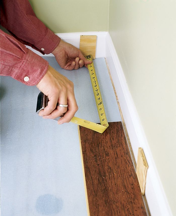 Man Installs First Course Of Floating Floor Planks