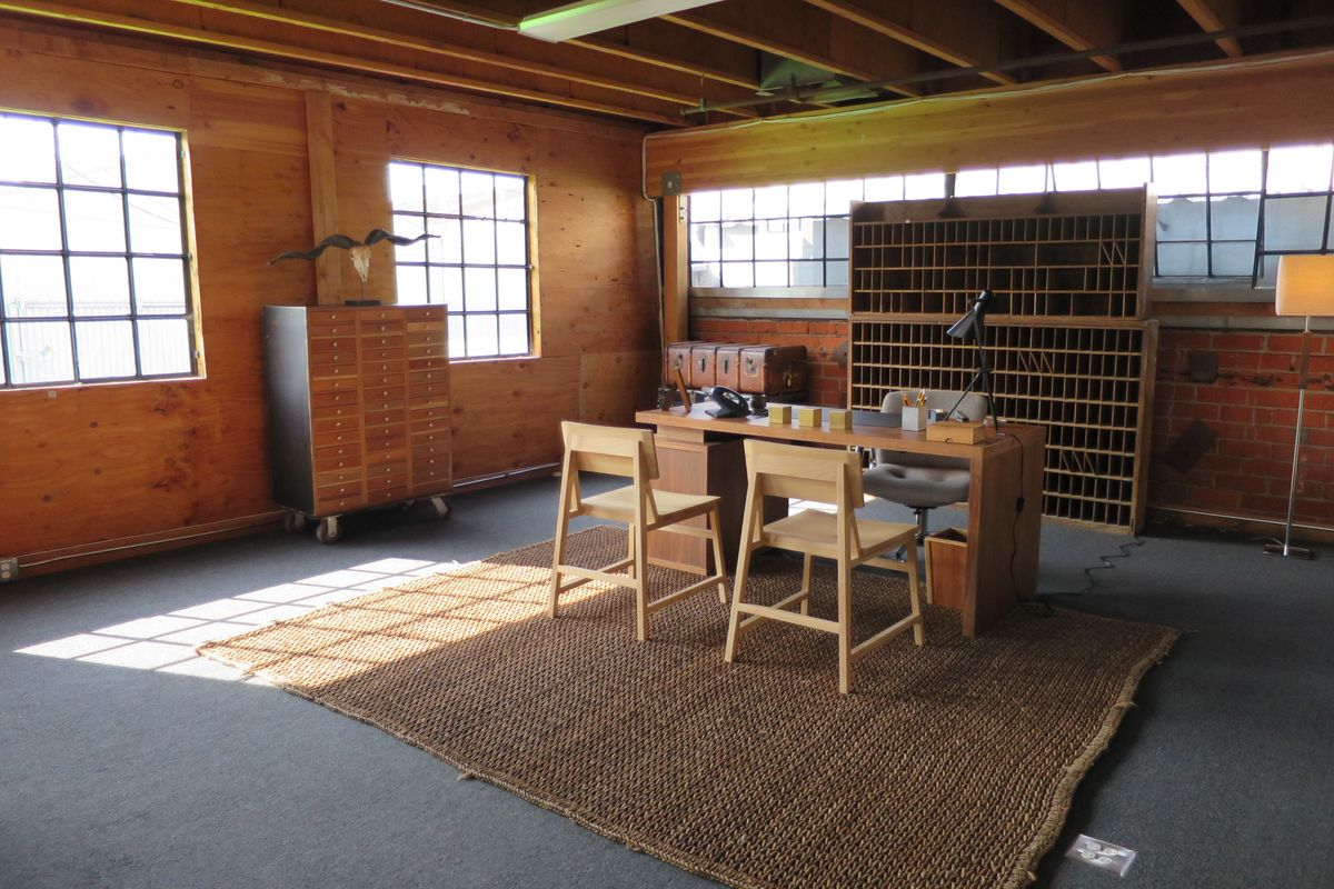 Interior of office set into corner of warehouse space with plain wood furniture.