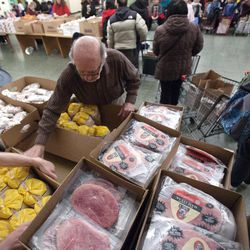 In this Thursday, March 29, 2012 photo, Paul Farris, second from left, of Boston, distributes hams and chickens in the Franciscan Food Center food pantry at St. Anthony Shrine in Boston. Ham prices have been higher than usual for the past two years because the cost of pig feed has gone up.