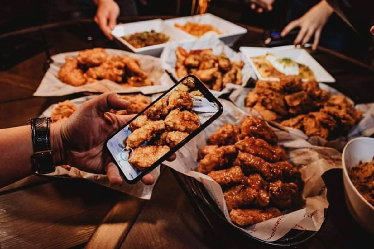 A table filled with plates of chicken pieces fried in 100% extra virgin oil from BB.Q Chicken.