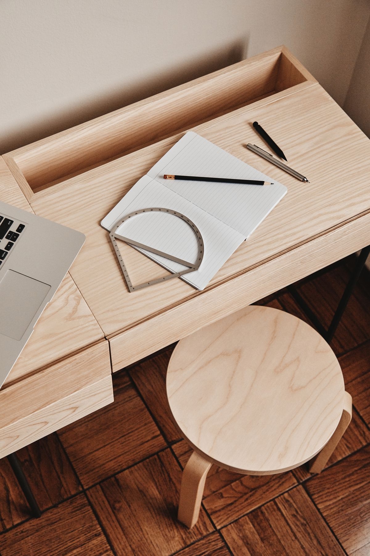 An overhead view of a pale wood desk with a notebook and pencils on top.