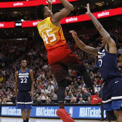 Utah Jazz's Donovan Mitchell (45) shoots as Minnesota Timberwolves' Jeff Teague (0) defends during the second half of an NBA basketball game Friday, March 2, 2018, in Salt Lake City. The Jazz won 116-108. (AP Photo/Kim Raff)