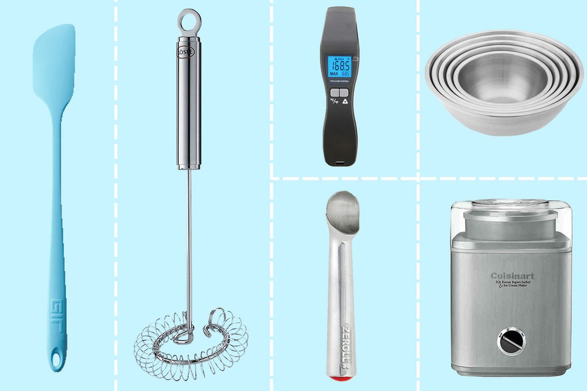 An ice cream maker, whisk, spatula, scoop, bowls, and thermometer laid out on a light blue grid