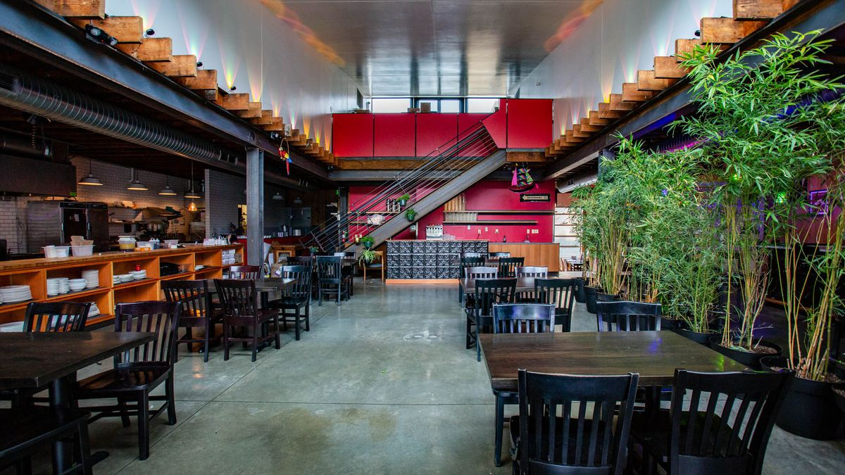 The dining room at HoneyHole in the Central District, with the kitchen to the left, the bar to the right, and a staircase agains a red wall in the middle