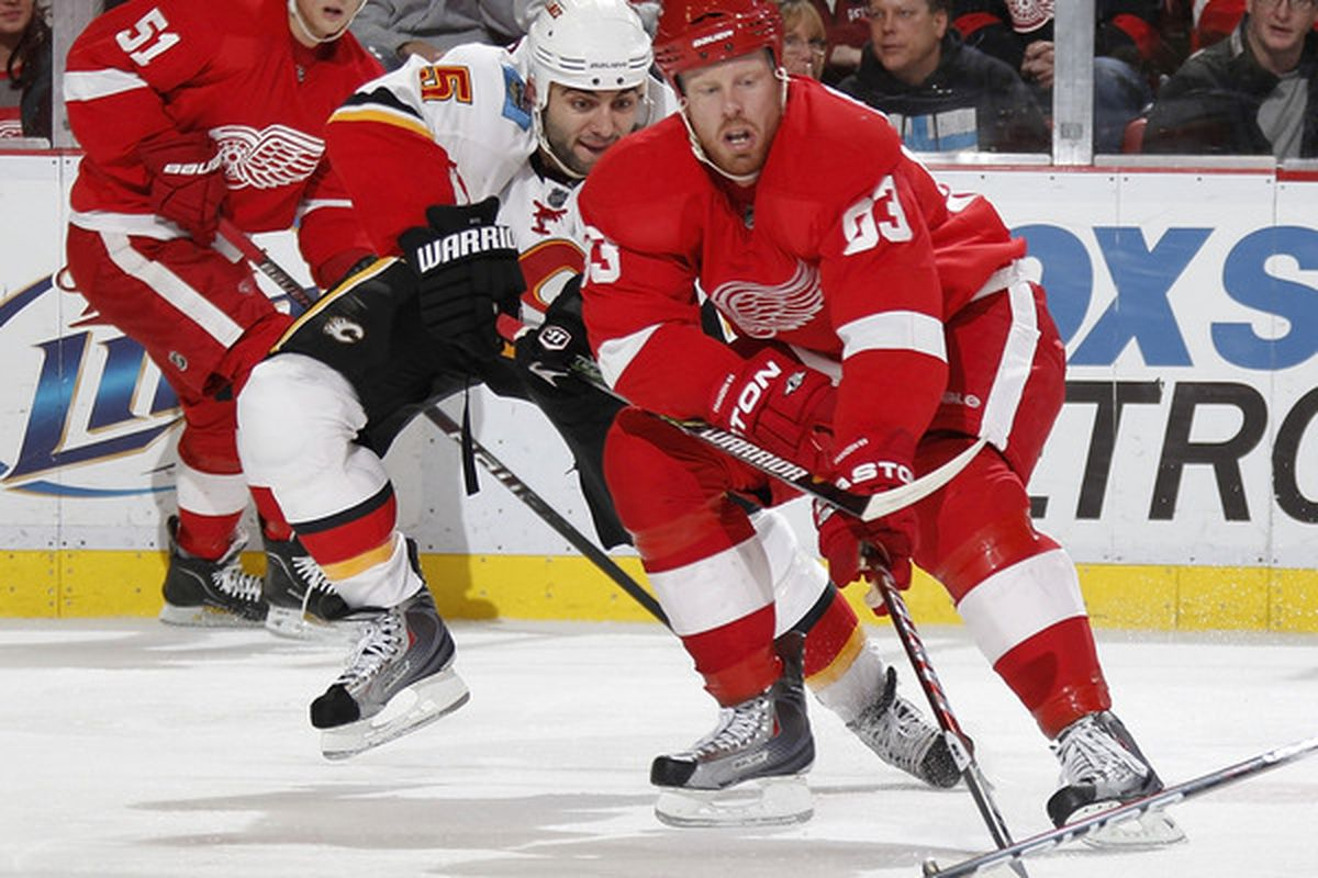 DETROIT - OCTOBER 21: Johan Franzen #93 of the Detroit Red Wings tries to control the puck in front of Mark Giordano #5 of the Calgary Flames on October 21 2010 at Joe Louis Arena in Detroit Michigan.  (Photo by Gregory Shamus/Getty Images)