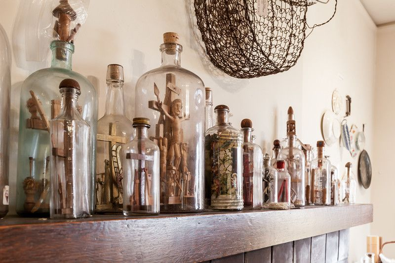 A shelf with multiple glass jars filled with religious objects.