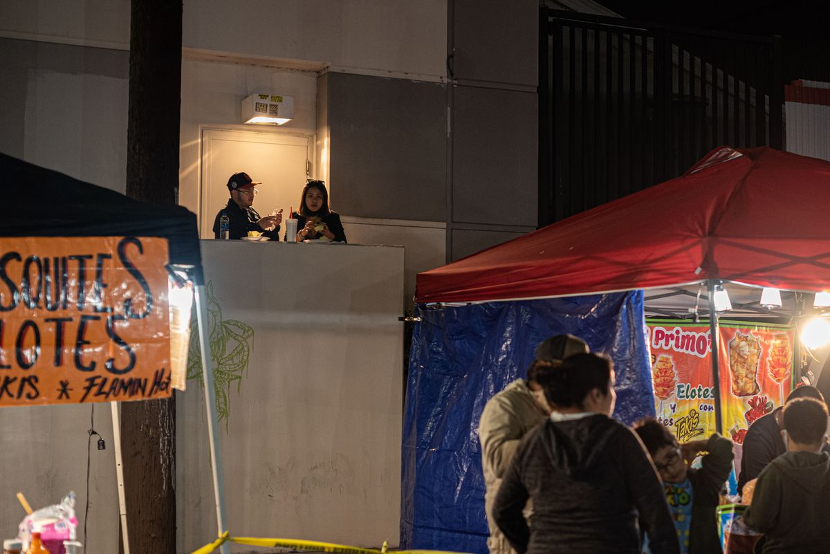 A couple stands above the fray eating food at a night market.