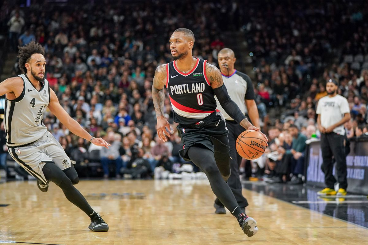 Portland Trail Blazers guard Damian Lillard dribbles in front of San Antonio Spurs guard Derrick White in the second half at the AT&T Center.