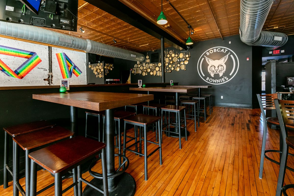Rainbow strips are painted on a white wall with a Bobcat Bonnie's logo painted in black and white nearby at the Ferndale restaurant's dining room.