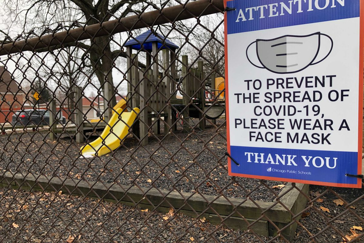 A closed Chicago school playground has a sign for wearing face masks due to COVID-19.