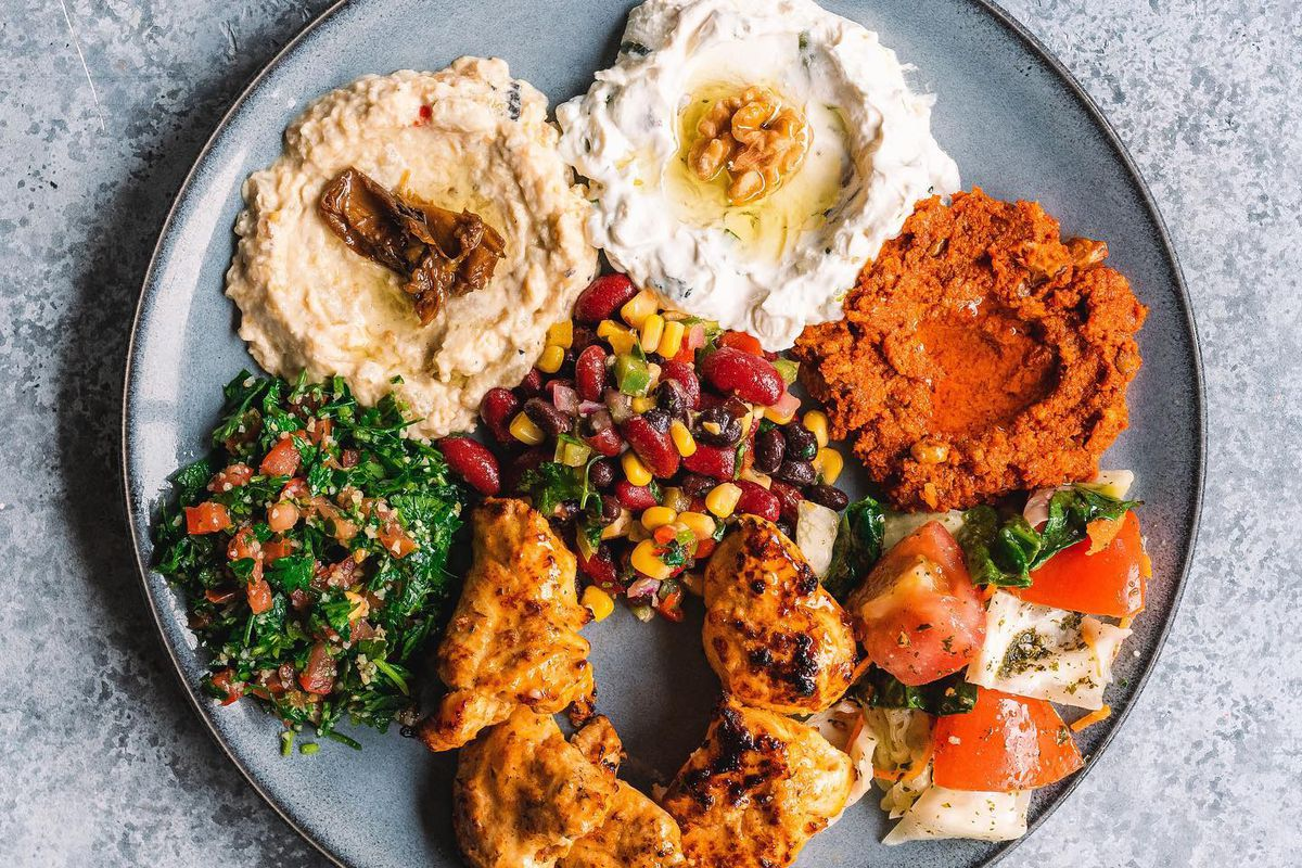 a platter with hummus, grilled chicken, baba ganoush, falafel and more