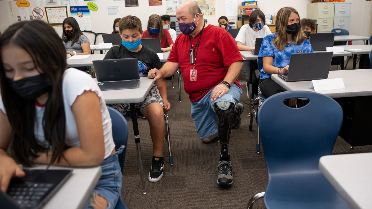 Bill Coleman, a sixth grade teacher, chats with Jerry Oyler during class at Nibley Park School in Salt Lake City.